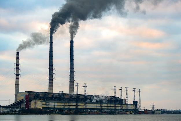 Linie wysokiego napięcia i rury elektrowni węglowych z czarnym dymem unoszącym się w zanieczyszczającą atmosferę.