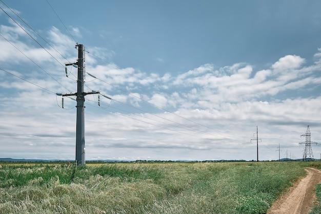 Linie wysokiego napięcia, krajobraz na zielonym polu w południe, jasny słoneczny dzień, błękitne niebo z chmurami. zaopatrzenie w energię dla życia miejskiego