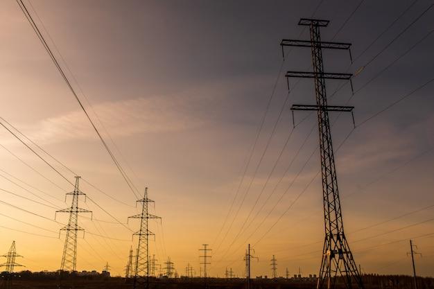 Linie wysokiego napięcia o zachodzie słońca. stacja dystrybucji energii elektrycznej