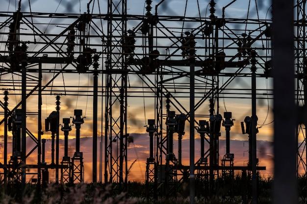 Linie wysokiego napięcia stacji dystrybucji energii elektrycznej o zachodzie słońca