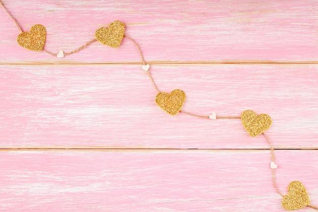 Liny jutowe ze złotymi brokatem serca i konfetti serca na różowym tle