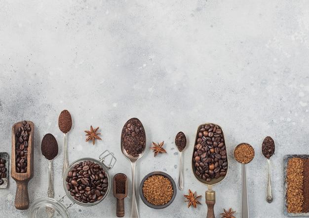 Liofilizowane granulki kawy rozpuszczalnej z mieloną kawą i ziarnami w różnych łyżkach i szufelkach na czarnym tle ze szklanym słojem i stalowymi płytkami. miejsce na tekst