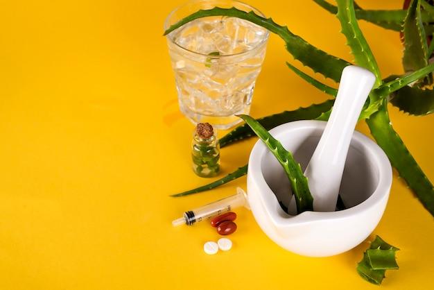 Liść aloesu, biała zaprawa pełna pokrojonego aloesu i butelek żelu lub naparu z aloesu.