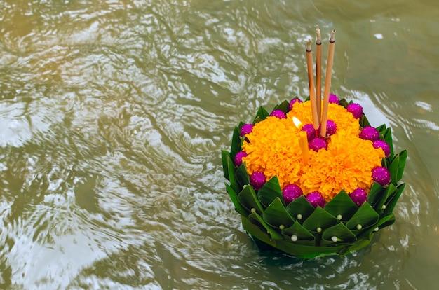 Liść bananowca krathong pływający po rzece podczas pełni księżyca w tajlandii lub festiwalu loy krathong.