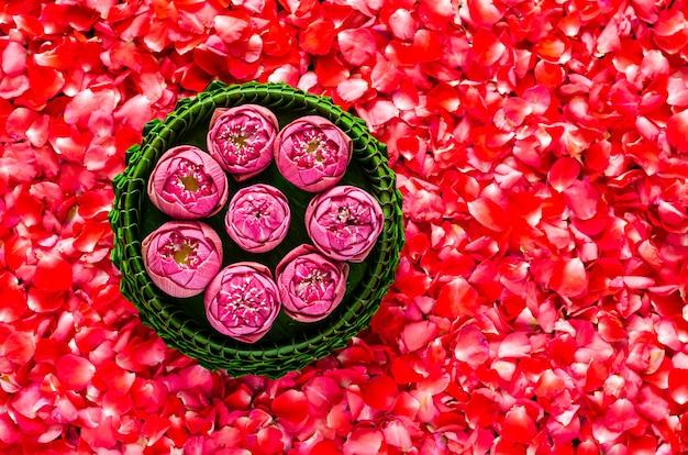 Liść bananowca krathong z kwiatami lotosu dla tajlandii full moon lub festiwal loy krathong na tle czerwonych płatków róż.