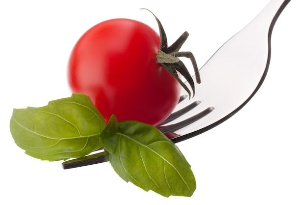 Liść bazylii i pomidor cherry na widelec na białym tle wyłącznik. koncepcja zdrowego odżywiania.
