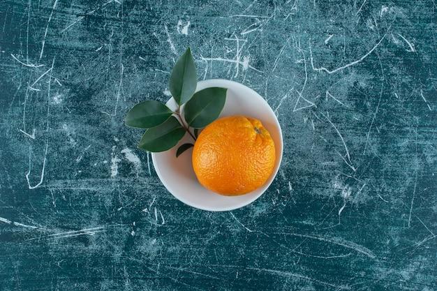Liść i mandarynka w misce, na marmurowym tle. zdjęcie wysokiej jakości
