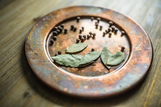 Liść laurowy i nowa przyprawa na talerzu.