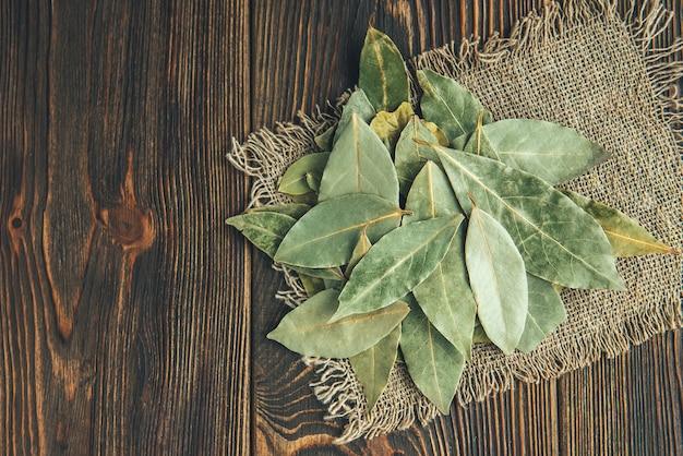 Liść laurowy na podłoże drewniane.