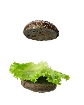 Liść zielonej sałaty leży na połowie czarnej okrągłej bułki, a jedzenie jest izolowane na białej powierzchni