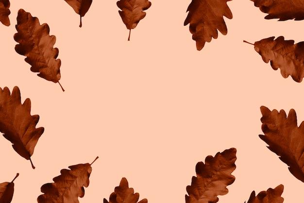 Liście dębu pomalowane rdzawopomarańczową ramką na beżowym tle październikowa jesienna karta z miejscem na kopię