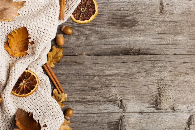 Liście, dzianinowy koc, sucha pomarańcza, cynamon i żołędzie na starym drewnianym stole