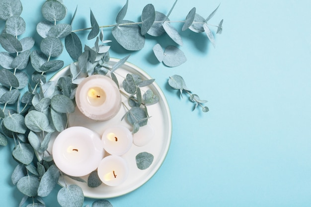Liście eukaliptusa i świece na niebieskim tle