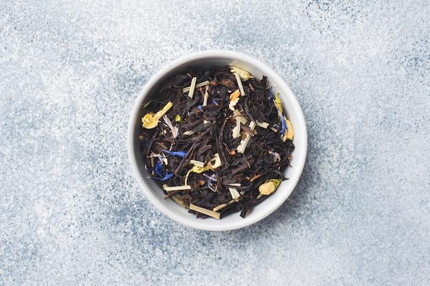 Liście herbaty do warzenia w misce na szarym tle.