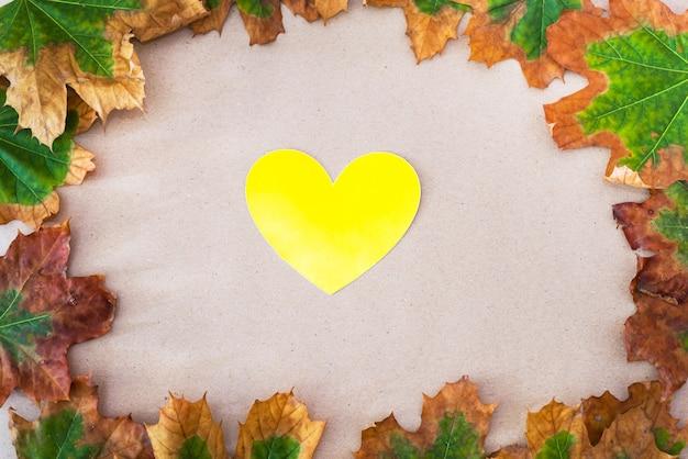 Liście i żółte serce. koncepcja jesień.