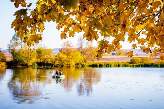 Liście klonu złocistego nad rzeką jesienią. rybacy w łodzi na rzece