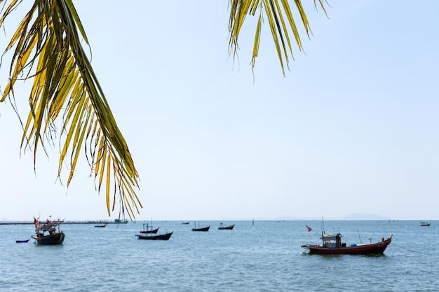 Liście kokosowe z zamazanym tłem morza i łodzi.