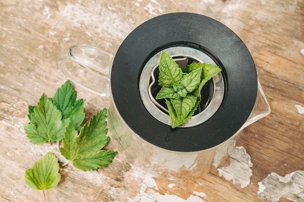 Liście mięty i porzeczki na herbatę. zdrowa herbata z roślin ogrodowych. przenieś powstałą mieszaninę do czajnika, dodaj czarną herbatę liściastą i kilka listków mięty.