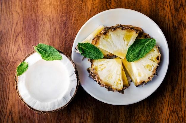Liście mięty leżą na kawałkach ananasa i kokosa