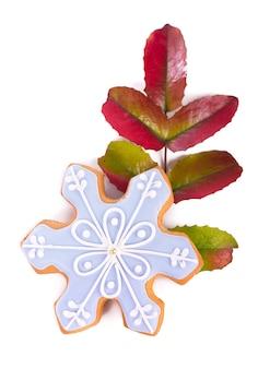 Liście ostrokrzewu i świąteczne pierniki na białym tle