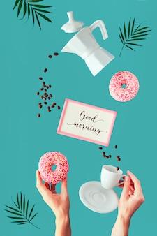 """Liście palmowe, ramka z tekstem """"dzień dobry"""". wibrująca ściana zielonej mięty lewitująca kawa i pączki w rękach. latające ziarna kawy. ceramiczny ekspres do kawy, filiżanka espresso trzymana w ręku dziewczyny."""