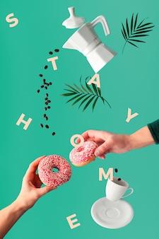 """Liście palmowe, ramka z tekstem """"stay home"""". kawa lewitacyjna i dwa różowe pączki w rękach. mucha linia ziaren kawy. ceramiczny ekspres do kawy i filiżanka espresso."""