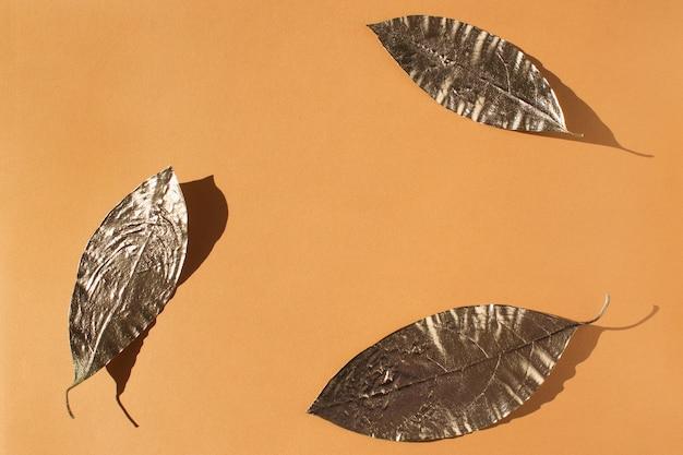 Liście pomalowane na złoto na pomarańczowo.