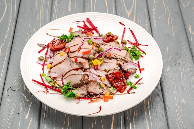 Liście sałaty z pokrojoną pieczoną wołowiną i suszonymi pomidorami cherry