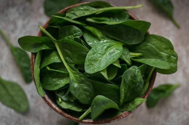 Liście świeżego szpinaku baby w misce. ciemnozielone liście organiczne. koncepcja stylu życia zdrowej żywności wegańskiej. widok z góry, zbliżenie