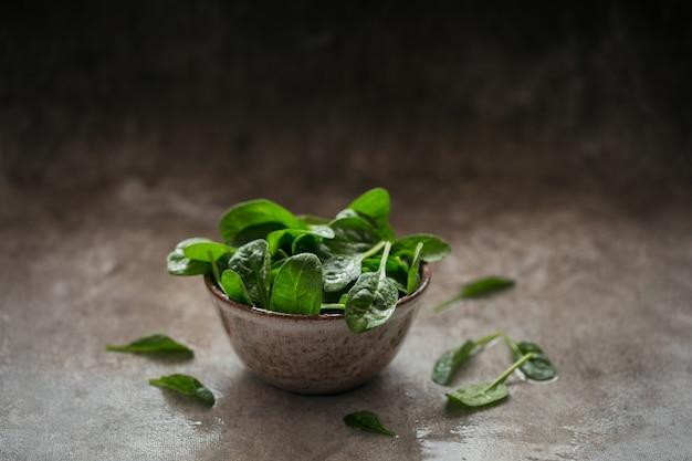 Liście świeżego szpinaku baby w misce. ciemnozielone liście organiczne. koncepcja zdrowego stylu życia wegańskiego jedzenia