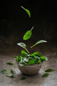 Liście świeżego szpinaku baby w misce. latające liście. ciemnozielone liście organiczne. koncepcja zdrowego stylu życia wegańskiego jedzenia