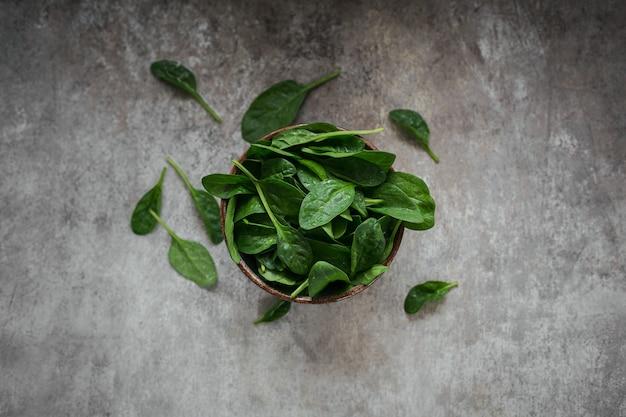 Liście świeżego szpinaku baby w misce. widok z góry ciemnych organicznych zielonych liści. koncepcja zdrowego stylu życia wegańskiego jedzenia