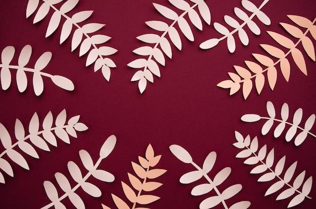 Liście wykonane z papieru na bordowym tle