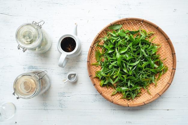 Liście zielonej herbaty na drewnianej tacy z herbatą w butelce