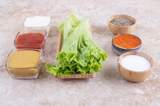 Liście zielonej sałaty z sosami i przyprawami.
