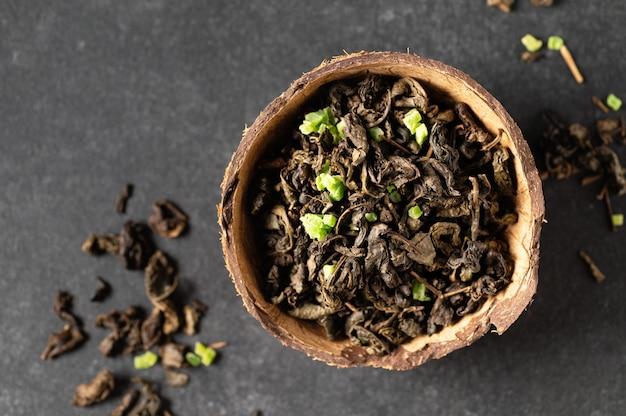 Liście zielonej suchej herbaty w misce kokosowej z posypanymi liśćmi