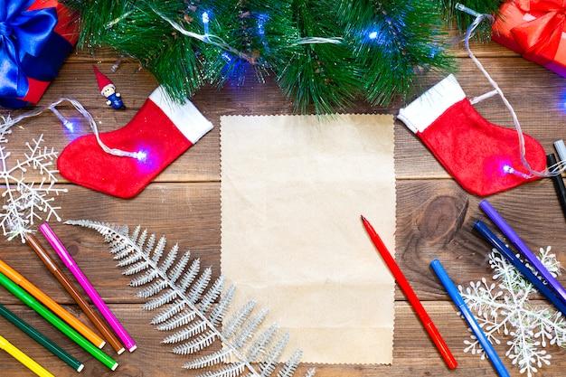 List dla dzieci do świętego mikołaja. mała dziewczynka pisze list z wielobarwnymi pisakami na drewnianym stole