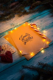 List do drodzy mikołaj na niebieskim drewnianym stole w duchu bożego narodzenia.