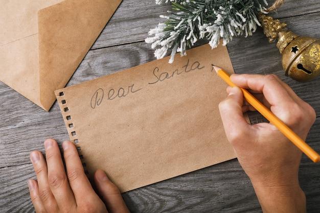 List do ozdób choinkowych świętego mikołaja i kartka papieru z miejscem na powitanie na starej tablicy