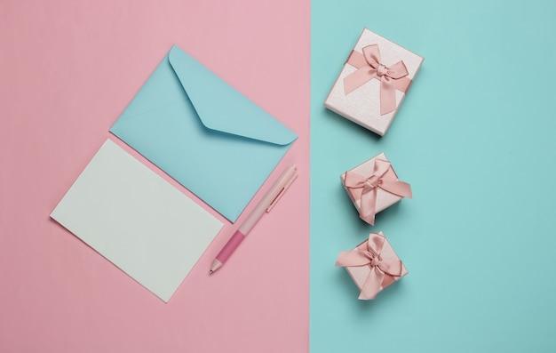 List do świętego mikołaja. koperta z listem i piórem, pudełka prezentów na różowym niebieskim tle. boże narodzenie mieszkanie leżało. widok z góry