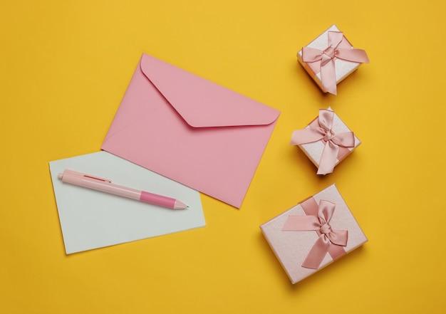 List do świętego mikołaja. koperta z listem i piórem, pudełka prezentów na żółtym tle. boże narodzenie mieszkanie leżało. widok z góry