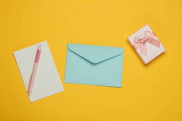 List do świętego mikołaja. koperta z listem i piórem, pudełko z prezentami na żółtym tle. boże narodzenie mieszkanie leżało. widok z góry