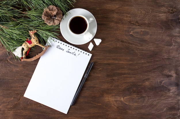List do świętego mikołaja na stole z herbatą i świątecznymi ozdobami