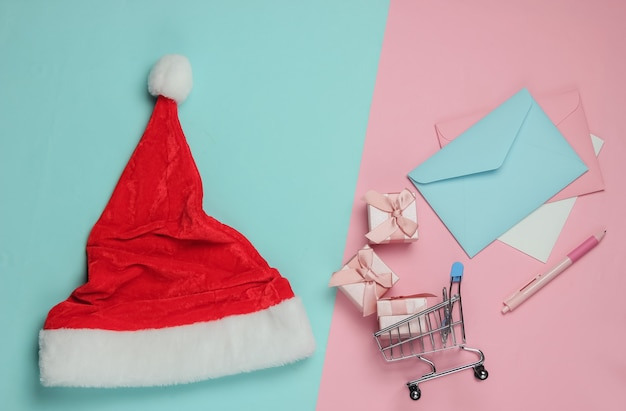 List do świętego mikołaja. santa hat, koperta z listem i długopisem, pudełka z prezentami i wózek na zakupy na różowym niebieskim tle pastelowych. boże narodzenie mieszkanie leżało. widok z góry