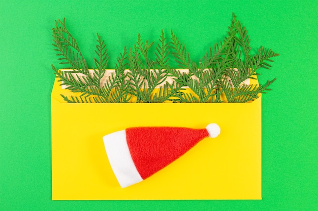 List do świętego mikołaja. święty mikołaj czerwony kapelusz, koperta, świerkowa gałąź. koncepcja nowego roku i świąt. widok z góry na płasko, z miejsca na kopię.