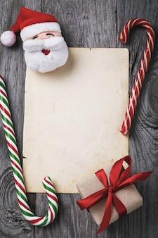 List do świętego mikołaja z cukierkami i pudełkiem prezentowym