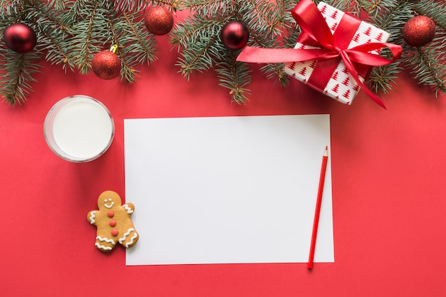 List do świętego mikołaja z mlekiem, ciasteczka, pierniki na czerwono. widok z góry i miejsce na tekst. leżał płasko.