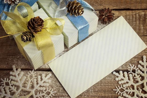 List gratulacyjny, prezenty świąteczne, płatki śniegu, świąteczne zabawki i guzy na starym drewnianym tle, przyciemniony obraz