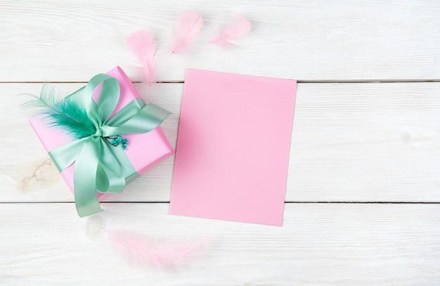 List i różowe pudełko na jasnym tle drewnianych. widok z góry z miejscem na kopię.
