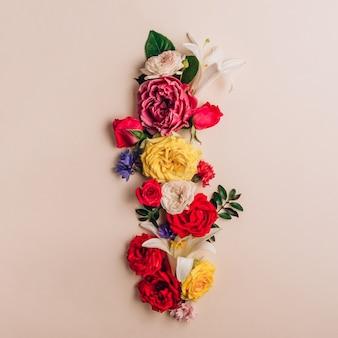 List i wykonany z prawdziwych naturalnych kwiatów na beżowym tle. czcionka kwiatowa. koncepcja kreatywna lato. widok z góry. płaskie ułożenie